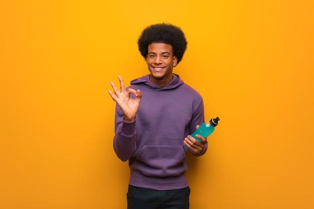 エネルギードリンクを持っている若いアフリカ系アメリカ人のフィットネス男は、大丈夫なジェスチャーをする陽気で自信を持っています