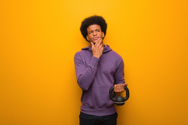 Young african american fitness man holding a dumbbell doubting and confused