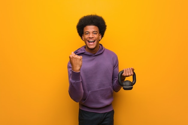 Young african american fitness man holding a dumbbell surprised and shocked