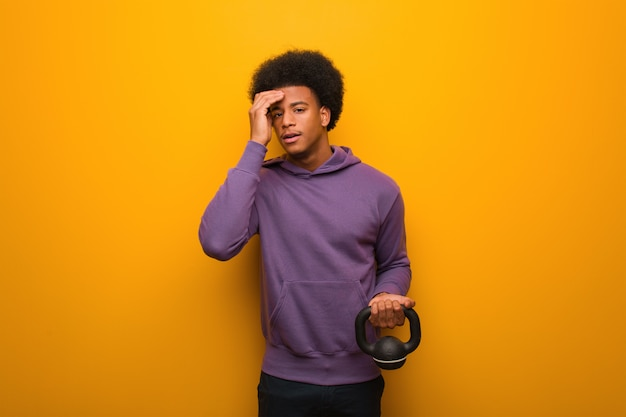 Young african american fitness man holding a dumbbell worried and overwhelmed