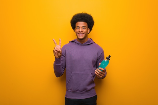 Young african american fitness man holding an energy drink fun and happy doing a gesture of victory