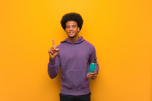 Young african american fitness man holding an energy drink showing number one