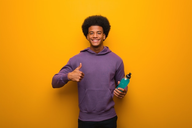 Young african american fitness man holding an energy drink smiling and raising thumb up