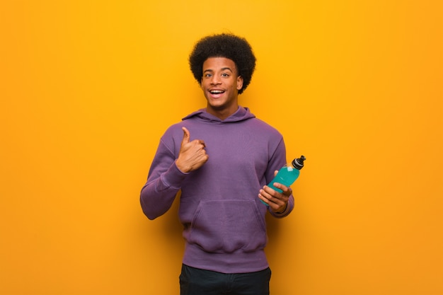 Young african american fitness man holding an energy drink surprised, feels successful and prosperous