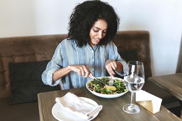레스토랑에서 샐러드를 먹는 젊은 아프리카 계 미국인 여자. 카페에 앉아 샐러드를 먹는 검은 곱슬 머리를 가진 아름다운 소녀