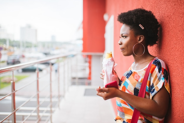 Young african american girl holding burger in her hands outdoor