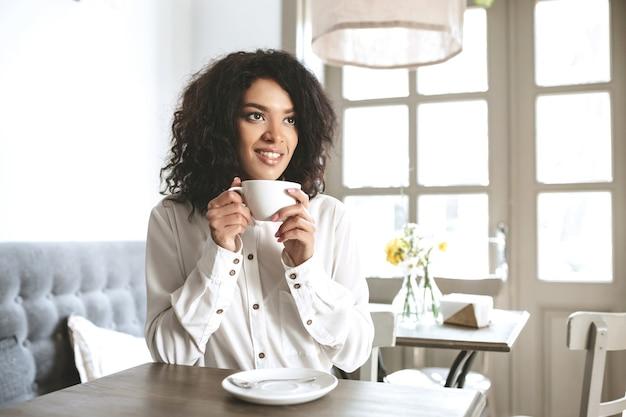 手にコーヒーを飲みながらレストランに座っている白いシャツの若いアフリカ系アメリカ人の女の子。カフェでコーヒーを飲むかわいい笑顔の女の子