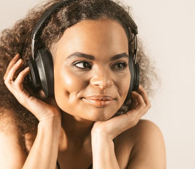 Молодая афро-американская девушка слушает музыку в наушниках