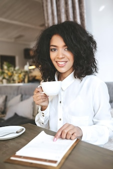 Young african american girl sitting in restaurant with cup of coffee