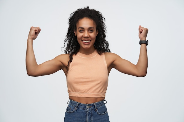 Young african american girl smiles broadly and show her muscles
