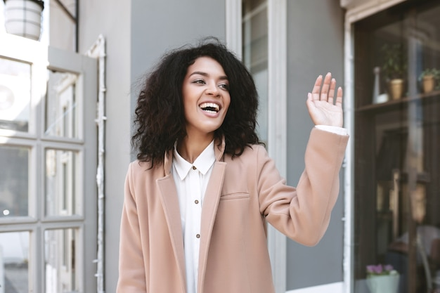 Молодая афро-американская девушка улыбается и показывает привет жест на улице жизнерадостная девушка стоит в бежевом пальто и белой рубашке портрет красивой дамы машет рукой и здоровается
