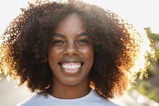 街の屋外カメラで笑っている若いアフリカ系アメリカ人の女の子-顔に焦点を当てる