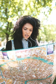 Молодая афро-американская девушка стоит на улице и пытается найти правильное направление на карте в ее руках