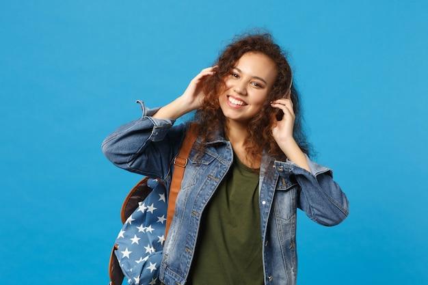 Giovane studentessa teenager della ragazza afroamericana in vestiti del denim, cuffie dello zaino isolate sulla parete blu