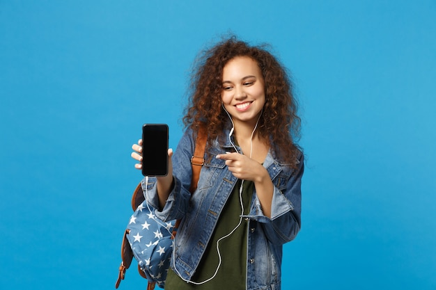 Young african american girl teen student in denim clothes, backpack headphones isolated on blue wall