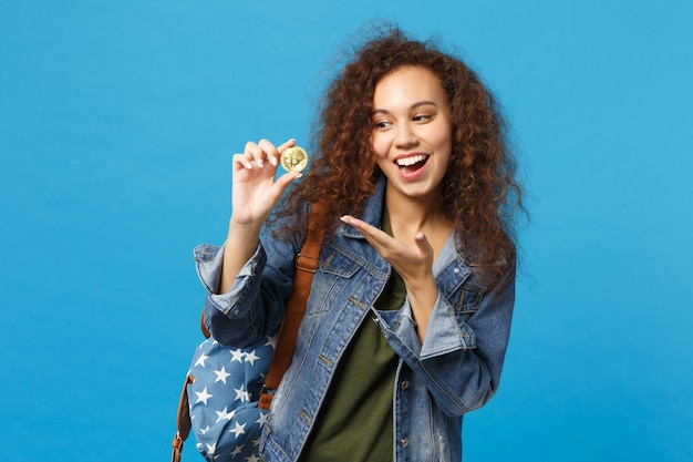 Young african american girl teen student in denim clothes, backpack hold bitcoin isolated on blue wall