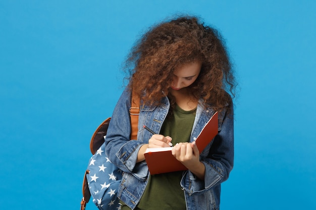 Giovane studentessa teenager della ragazza afroamericana in vestiti del denim, libri della tenuta dello zaino isolati sulla parete blu