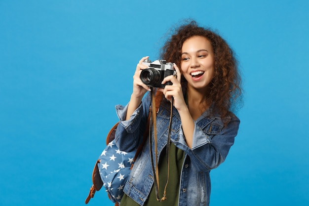 Young african american girl teen student in denim clothes backpack hold camera isolated on blue wall