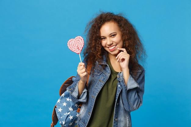 Giovane studentessa teenager della ragazza afroamericana in vestiti del denim, caramella della tenuta dello zaino isolata sulla parete blu