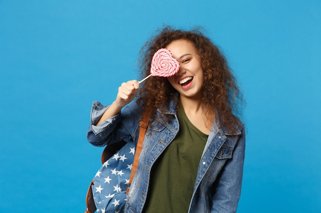 Young african american girl teen student in denim clothes, backpack hold candy isolated on blue wall