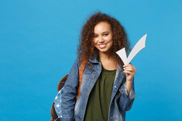 Giovane studentessa teenager della ragazza afroamericana in vestiti del denim, controllo della tenuta dello zaino isolato sulla parete blu
