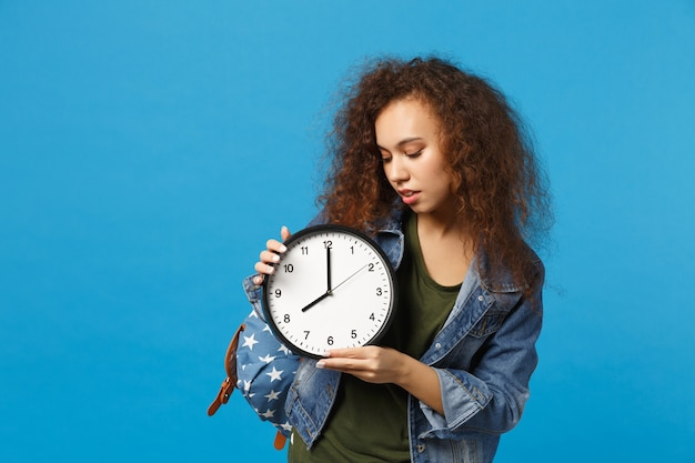 Young african american girl teen student in denim clothes, backpack hold clock isolated on blue wall