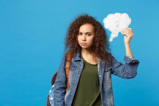 Giovane studentessa teenager della ragazza afroamericana in vestiti del denim, orologio della tenuta dello zaino isolato sulla parete blu