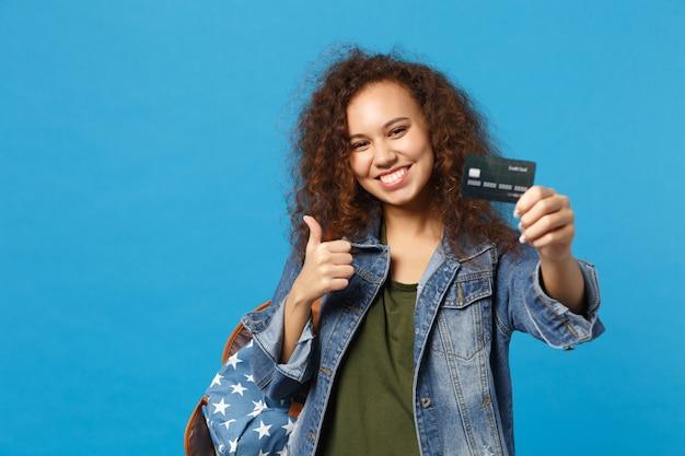 Giovane studentessa teenager della ragazza afroamericana in vestiti del denim, carta di credito della tenuta dello zaino isolata sulla parete blu