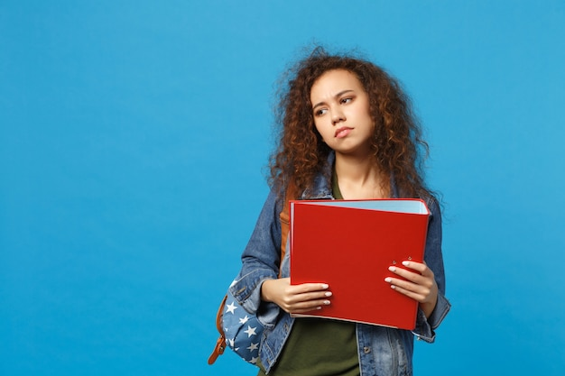 Young african american girl teen student in denim clothes backpack hold folder isolated on blue wall