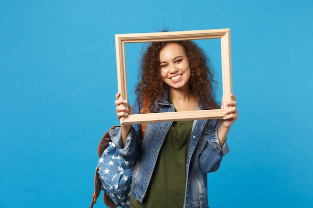 Young african american girl teen student in denim clothes, backpack hold frame isolated on blue wall