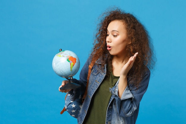 Young african american girl teen student in denim clothes, backpack hold globe isolated on blue wall