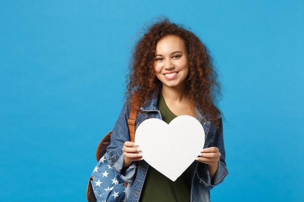 Giovane studentessa teenager della ragazza afroamericana in vestiti del denim, cuore della tenuta dello zaino isolato sulla parete blu