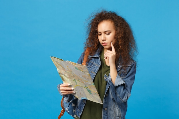 Young african american girl teen student in denim clothes, backpack hold map isolated on blue wall