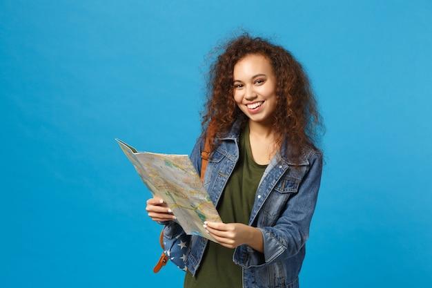 Giovane studentessa teenager della ragazza afroamericana in vestiti del denim, mappa della tenuta dello zaino isolata sulla parete blu