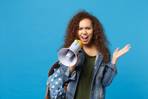 Young african american girl teen student in denim clothes, backpack hold megaphone isolated on blue wall