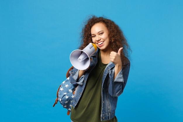 Giovane studentessa teenager della ragazza afroamericana in vestiti del denim, megafono della tenuta dello zaino isolato sulla parete blu