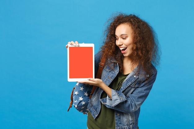 Giovane studentessa teenager della ragazza afroamericana in vestiti del denim, pc del rilievo della tenuta dello zaino isolato sulla parete blu della parete