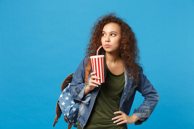 Young african american girl teen student in denim clothes, backpack hold paper cup isolated on blue wall