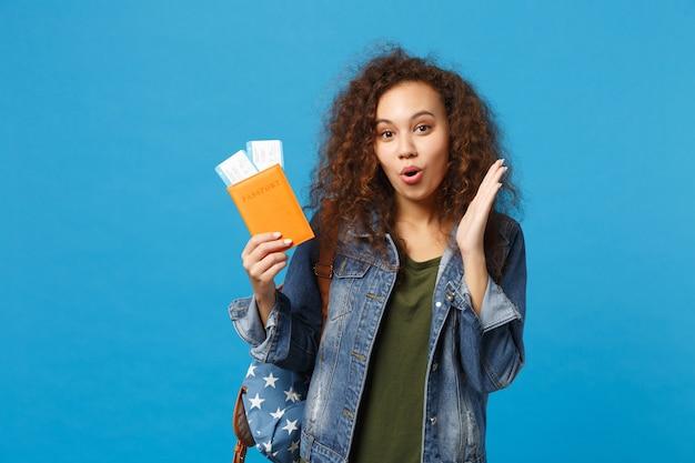 Giovane studentessa teenager della ragazza afroamericana in vestiti del denim, passaggio della tenuta dello zaino isolato sulla parete blu