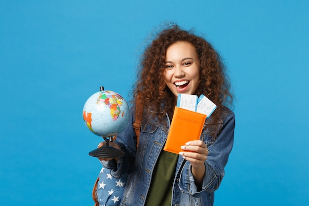 Young african american girl teen student in denim clothes, backpack hold pass isolated on blue wall