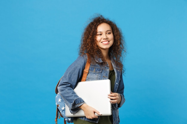 Young african american girl teen student in denim clothes, backpack hold pc isolated on blue wall