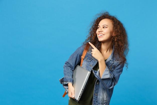Giovane studentessa teenager della ragazza afroamericana in vestiti del denim, pc della tenuta dello zaino isolato sulla parete blu