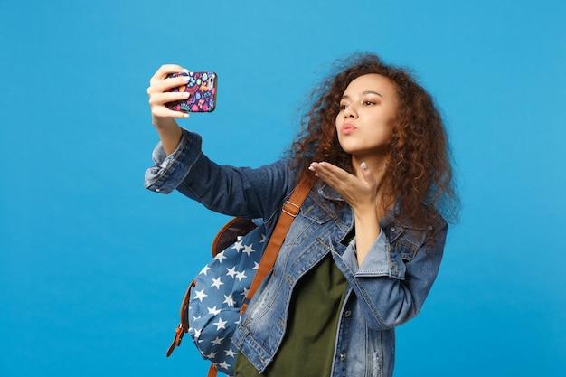 Giovane studentessa teenager della ragazza afroamericana in vestiti del denim, telefono della tenuta dello zaino isolato sulla parete blu