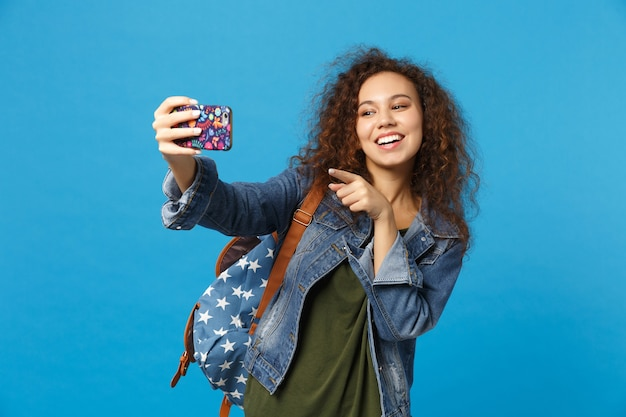 Young african american girl teen student in denim clothes, backpack hold phone isolated on blue wall