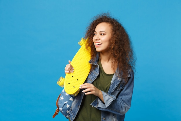 Young african american girl teen student in denim clothes, backpack hold skate isolated on blue wall