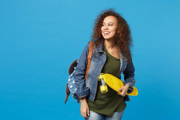 Giovane studentessa teenager della ragazza afroamericana in vestiti del denim, pattino della tenuta dello zaino isolato sulla parete blu