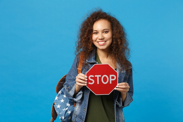 Young african american girl teen student in denim clothes, backpack hold stop isolated on blue wall