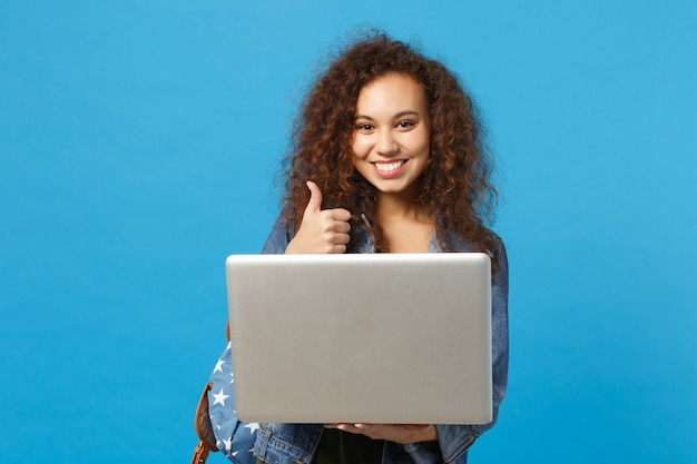 Giovane studentessa teenager della ragazza afroamericana in vestiti del denim, lavoro dello zaino sul pc isolato sulla parete blu