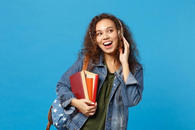 Молодая афро-американская девушка-подросток-студент в джинсовой одежде, рюкзак с наушниками, изолированные на синей стене