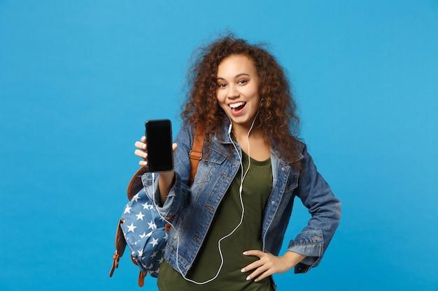데님 옷에 젊은 아프리카 계 미국인 여자 십대 학생, 파란색 벽에 고립 된 배낭 헤드폰